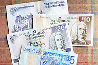 Scottish banknotes from The Royal Bank of Scotland £5, £10 £20 on traditional Scottish tartan background