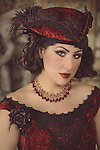 Close up of a young dark-haired woman with heavy makeup and historical fancy clothing with a strong gaze