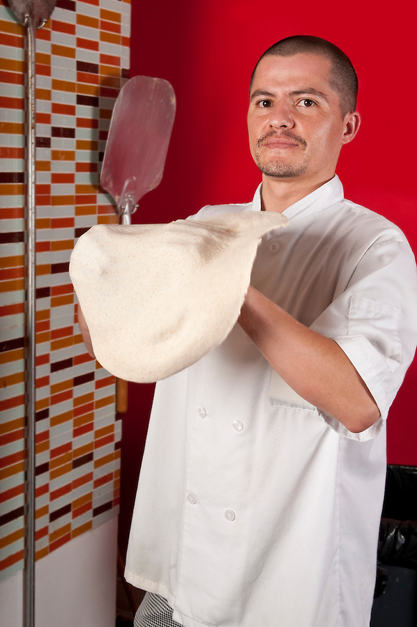 Young hispanic immigrant cook kneading pizza dough very happy.