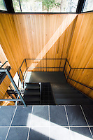 A metal staircase ascends a wood-lined stairwell to the roof terrace