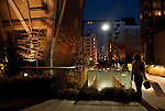 People walking on the Highline (public park on an old elevated train line) at night in New York City with a view of the stairs that exit onto West 23rd Street