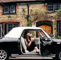 Daisy Lowe eating a cup cake in her Figaro in front of the family house in Hampshire