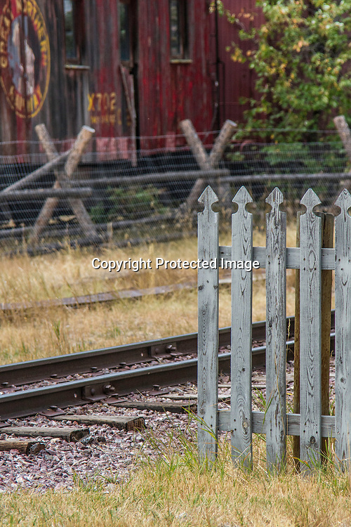A fence stands next to a railroad trach with an old train in the background.