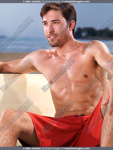 Young man with a surfboard enjoying his time at the beach