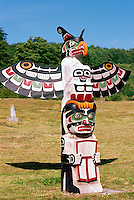 Kwakwaka'wakw (Kwakiutl) Memorial Totem Pole on Namgis Burial Grounds, Alert Bay, Cormorant Island, BC, British Columbia, Canada - Thunderbird over Man holding Copper