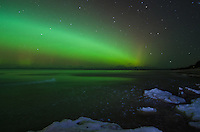 A bright Northern Lights band stretching over the frozen Lake Superior shoreline. Marquette, MI