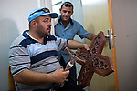 Mcc0070043 . Daily Telegraph<br /> <br /> DT News<br /> <br /> Ryin inspects a crucifix to be hung in the camp church .<br /> <br /> Ryin Farouk Benham, who lives with his family in the Virgin Mary Camp for homeless Christians that escaped Mosul when ISIS took the city .<br /> <br /> Baghdad 13 May 2016