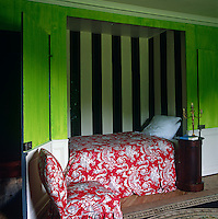 This bedroom has a single bed built into a black and white striped niche in a lime-green wall