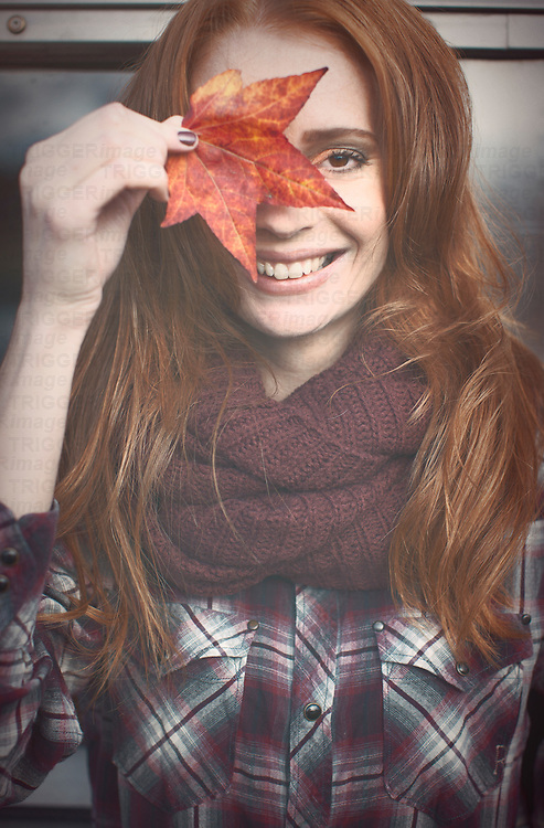 smiling woman with leaf in autumn