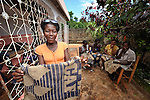 A member of Haitian Artisans for Peace International (HAPI), based in the southern Haitian village of Mizak, displays one of the bags, crafted from recycled coffee sacks, that the group is producing. The bags will be provided to delegates to the 2012 General Conference of The United Methodist Church. Each bag will carry the embroidered logo of the Advance.