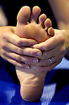 Hands grasped around a food during stretching at an Ashtanga Yoga class instructed by Casey Palmer at the Mini-Mavericks Sports Club..