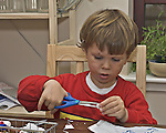 Boy playing with scissors and paper