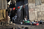 A woman does her family's laundry in front of her meager home in Cite Soleil, a sprawling poor portion of Port-au-Prince, Haiti.