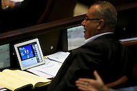 Knesset member Muhammad Barakeh watches cartoons during a plenum session voting on the state budget, in the Knesset, Israel's Parliament, in Jerusalem, late night July 29, 2013. The Knesset approved the State Budget at second and third readings in the early hours of Tuesday morning in a 58-43 vote, following a 15-hour parliamentary session. Photo by Oren Nahshon