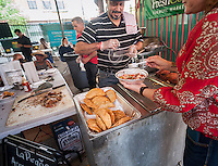Puerto Rican cuisine is served at the kick-off of the annual Vendy Plaza at  La Marqueta in the East harlem neighborhood of New York on Sunday, May 24, 2015. The plaza area, La Marqueta Retoña, hosts a weekly vendors market drawing on food entrepreneurs from the streets around the city. (© Richard B. Levine)
