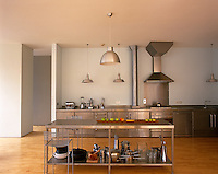 A stainless steel kitchen in an open-plan loft with a movable work island