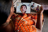 "Shardaben holds photographs of her surrogacy jobs...Shardaben Kantiben, 31; Husband is Kantibhai Motibhai (37).3 children --- 2 girls -  Usha(15) and Lakshmi (18, in pink); 1 boy, Chintan (17).- Education costs for all three come to Rs. 15,000 per year.- Shardaben was a two-time surrogate. First time she gave birth to twin girls for a Taiwanese couple and the second time a boy for an Indian couple from America (photo on TV set because she's proud that it was a boy).- The second time she became emotional and they got a gold ring of Rs. 1,500 made for the boy, which they presented to the biological parents. They are not in touch with either couple..- From the two surrogacies, they earned a little over 700,000rupees..-200,000rupees will be given as dowry for Lakshmi's wedding..- They leased agricultural land (Rs. 2 lakhs for five years) which earns them Rs. 60,000-70,000 a year; they bought two buffaloes worth Rs. 60,000 and make almost 6000-7000 per month selling milk; they bought a motorbike for Rs. 25,000; they put some money into house repairs and the construction of toilets, and opened a fixed deposit in Shardaben's name for Rs. 1.5 lakh and one in the name of their son, Chintan, for Rs. 25,000..Quotes..""Everyone says they'll keep in touch and take down addresses and phone numbers but nobody looks back. And I guess it works well. Our main interest was in the money. Their main interest is in the baby."" - KantiBhai.""Their rules apply at the surrogate house. It does curtail the freedom. When I used to go, everybody would just be lying. They count the days when they can go back."" - Kantibhai.""Ours is natural birth but surrogacy is a man-made pregnancy. There's a lot of risk. She must have taken at least 300 injections."" - Kantibhai of his wife...The Akanksha Infertility Clinic is known internationally for its surrogacy program and currently has over a hundred surrogate mothers pregnant in their environmentally controlled surrogate houses. .Photo by Suzanne Lee"
