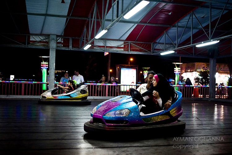 """A young couple  in their bumper car in """"Basraland,"""" a recently opened amusement park in the southern Iraqi city of Basra. ..Iraq's second city, Basra is attracting development and foreign investment. It has become relatively stable. Security, however, has come at the expense of cosmopolitanism. It is now almost exclusively Shiite Muslim, it's Sunni, Christian and Mandaean communities have dwindled to near near extinction. ..."""