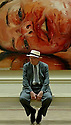 DAVID HOCKNEY AT THE ROYAL ACADEMY, LONDON, SITS IN FRONT OF A PAINTING BY