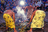 """Four Hawaiian men dressed in lavalavas ( traditional  garments) pull a roasted pig out of the """"""""imu"""""""" or earth oven at the Kona Village Resort. Seated tourists watch the ceremony."""