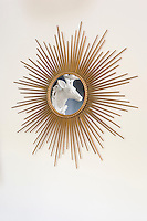 An alabaster stag's head displayed on a black wall in the dining room is seen reflected in a vintage sunburst mirror arranged opposite