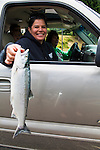 Terrie Brigham poses in her car with their fresh catch of a Sockeye Salmon at Cascade Locks, Oregon