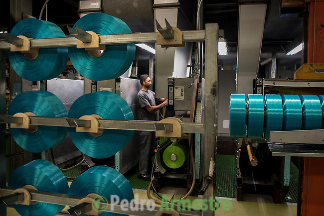 "An employee drives a forklift through the alleyways at a yarn processing plant in Angles, north-eastern Spain on November 6, 2015. Ecoalf, a Spanish Madrid-based firm founded in 2010, has already launched ""a new generation"" of clothes and accessories made from plastic bottles, old fishing nets and used tires found on land.  © Pedro ARMESTRE"
