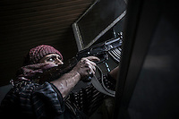 In this Wednesday, Oct. 24, 2012 photo. An FSA soldier shoots his kalashnikov to the enemy troops as rebel fighters belonging to the Liwa Al Tawhid carry out a militar operation at the Moaskar front line, one of the battlefields in Karmal Jabl neighborhood, northeast of Aleppo City. (AP Photo/Narciso Contreras).