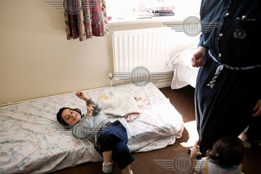 An Hasidic child lies on a mattress on the floor on their rented house. Hasidic families stay in Pentre Jane Morgan university accommodation when they holiday in Aberystwyth. Every other day, bread, milk and other supplies are brought from Kosher shops in London and resold from one of the rented houses on the campus.