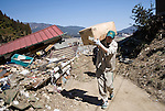 Kazuhiko Murakami, a delivery staffer for Kuroneko (Black Cat) express delivery service carries a parcel to a damaged home in the tsunami-trashed seaside town of Rikuzentakata, Iwate Prefecture, Japan on  7 April 20011.  .Photographer: Robert Gilhooly