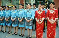 China. Province of Zhejiang. Hangzhou. Before the start of their shift, a group of waitresses and waiters stand on line outside the restaurant . © 2004 Didier Ruef