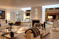 Cosy fur throws are placed within easy reach on comfortable armchairs and sofas in an informal living room and the alcoves on either side of the stone fireplace are mirrored to create an illusion of space
