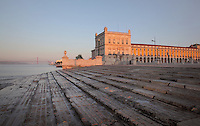 Buildings surrounding the Placa do Commercio or Commerce Square, Lisbon, Portugal, seen from the stepped banks of the river Tagus. The square was previously known as Terreiro do Paco or Palace Square as it was the site of the Pacos da Ribeira or Royal Ribeira Palace until it was destroyed in the 1755 earthquake. In the distance is the 25 de Abril suspension bridge crossing the Tagus river estuary. Picture by Manuel Cohen