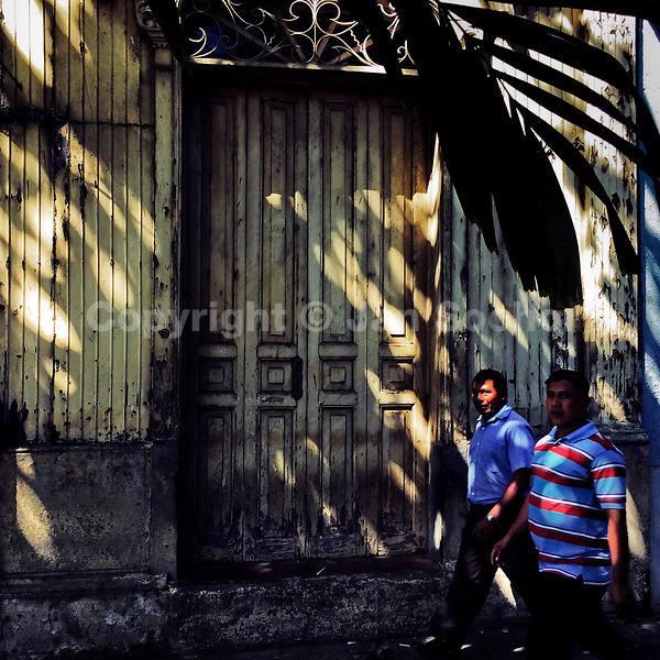 Salvadoran men walk in front of an unkept house with Spanish colonial architecture elements, built in the center of San Salvador, El Salvador, 12 November 2016.