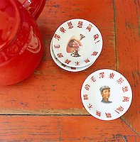 Detail of hand-painted saucers that bear the image of Mao Tse-Tung at different points in his career