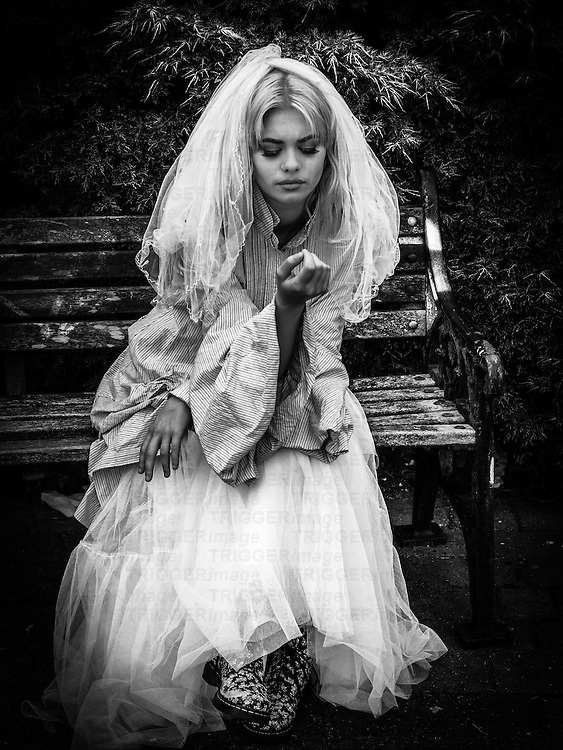 Young blonde model in bridal oiutfit looking bored,