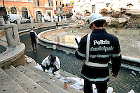 Rome. The collected of coins thrown by tourists into the Trevi Fountain for express a wish is made by the staff of Caritas of Rome and used to finance the Emporio Caritas..Operation that takes place once a week.The fountain was built by the architect Salvi (1735) in the time of Pope Clement XII, and decorated by several artists of Bernini's school.The municipal police check the collected of coins...La  raccolta delle monete gettate dai turisti dentro Fontana di Trevi per esprimere un desiderio viene effettuata dal personale della Caritas Diocesana di Roma  e servono a finanziare l?Emporio Caritas..Operazione che viene effettuata una volta a settimana.  La Polizia Municipale controla la regolarità della raccolta