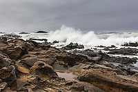 The rocky, tafoni-dimpled shore stretching southward is the landing point for waves that send spray high into the air.