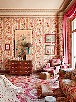 A traditional bedroom in tones of pink and red with rich floral pattern wallpaper and fabrics. The room is furnished with a comfortable sofa, armchair and an antique chest of drawers.