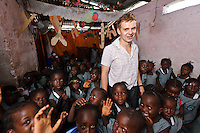 Rocco Falconer, founder of Planting Promise, at a school run by the charity, Freetown, Sierra Leone. Planting Promise is an organization dedicated to the development of education in Sierra Leone. Its aim is to bring opportunities to initiate self-run, self-supporting projects that offer real solutions to the difficulties facing the world's poorest country. They believe real and lasting development comes from below, from local projects that address specific needs, rather than large international models. To this end, they currently run five projects that aim to bring wealth into the country through business. The profits from these businesses are then used to support free education for children and adults...Through the combination of business with social progress, the charity hopes that they are providing real, lasting and profound changes for the better, by promoting sustainable and beneficial industry in the country, and putting it to the service to the needs of the people. As well as providing the income to fund the school, the farms will also be an example of successful commercial enterprise to teach the children in the school the viability of profit-making schemes that go beyond subsistence models, the only things the children of these desperately poor areas are accustomed to. By learning particular details of the challenges that they will face, the children will emerge from this school equipped to contribute in a real way to their society.