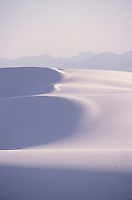 SAND DUNES<br /> (Variations Available)<br /> Barchan Ridge Dunes, White Sands Nat. Monument<br /> <br /> The dunes are formed of gypsum.  Deposits of selenite crystals are broken down into sand sized grains due to weather erosion. Prevailing wind carries the grains away forming constantly shifting dunes.