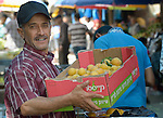 A man carries a box of apricots in the market in the Al-Shalti refugee camp in Gaza. Residents of the Palestinian territory are still reeling from the death and destruction of the 2014 war with Israel, and the continuing siege of the seaside territory by the Israeli military.