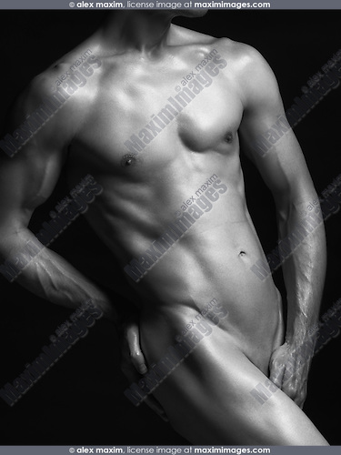 Young nude man with fit shiny naked body isolated on black background artistic black and white photo