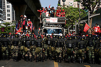 """""""Red Shirt"""" protesters are met by soliders in riot gear in Ploenchit one of Bangkok's busy business areas in the city centre."""
