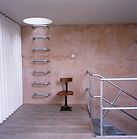 A ladder made of industrial tubular steel with rungs embedded in the bare plaster wall leads up through a circular skylight to the roof