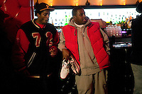 A man holds a pair of sneakers on display hoping to attract a buyer during Dunkxchange, a market held in a club in New York City, USA, where sneaker collectors trade and sell their rare shoes, 7 January 2007.<br />