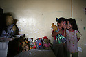 Zaynub, (l)age 5 whispers to her friend Zaina as they play with dolls in their family's room within a homeless community at the former Air Force headquarters in Baghdad, Iraq Oct 22, 2006. Hundreds of Iraqi families who cannot afford elevated post war housing costs have taken up residence in the abandoned air force base, making do with what they can.