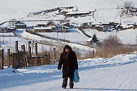 Altai Region, Siberia, Russia, 25/02/2011..An old woman walks from a village settlement near the proposed Siberian Coin casino project in the Altai mountains.