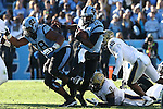 15 November 2014: UNC's Marquise Williams (12) is tripped up by Pitt's Todd Thomas (8) at the line of scrimmage. The University of North Carolina Tar Heels hosted the University of Pittsburgh Panthers at Kenan Memorial Stadium in Chapel Hill, North Carolina in a 2014 NCAA Division I College Football game. UNC won the game 40-35.