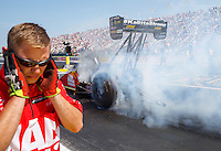 Sep 5, 2016; Clermont, IN, USA; A crew member holds his ears as NHRA top fuel driver Doug Kalitta does a burnout during the US Nationals at Lucas Oil Raceway. Mandatory Credit: Mark J. Rebilas-USA TODAY Sports